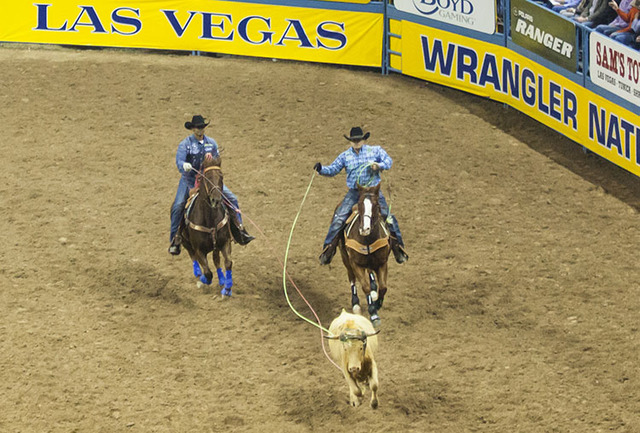 Junior Nogueira, left, and Kaleb Driggers compete during the team roping competition on the final night of the National Finals Rodeo at the Thomas & Mack Center in Las Vegas on Saturday, Dec.  ...