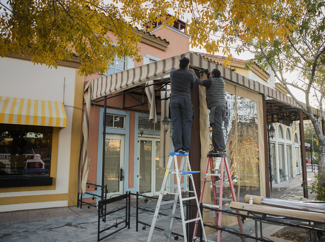 Workers place a screen at the soon to be open Mimi' & Coco' Bistro at MonteLago Village on Tuesday, Dec. 20, 2016. Lake Las Vegas' retail section is listed for sale at $10 million. Jeff Scheid ...
