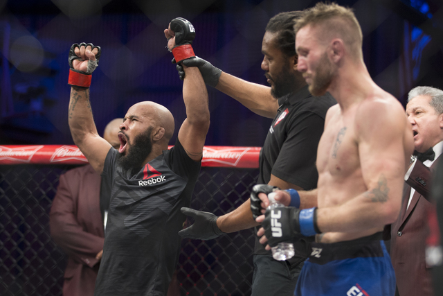 Demetrious Johnson, left, raises his arm in victory against Timothy Elliot in the The Ultimate Fighter 24 Finale flyweight title bout at the Palms hotel-casino Pearl Theater on Saturday, Dec. 3, 2 ...