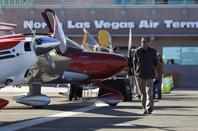 Mark Blackwood, floor supervisor at Lone Mountain Aviation, an aircraft repair company, walks past aircraft on display during an open house at the North Las Vegas Airport on Saturday, Dec. 10, 201 ...