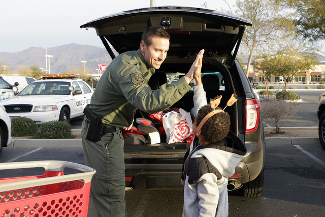 "North Las Vegas police officer Mark Mikolajczyk gets a high-five from Myles Vertisow, 8, after shopping at Target during the annual ""Shop with a Cop"" event on 7090 N. Fifth St. Wedne ..."