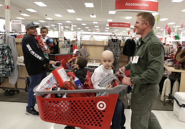 North Las Vegas police officer Peter Nelson checks out with Gavin Prince, 7, and his brother Brendan, 5, after shopping at Target during the annual ғhop with a CopӠevent on 7090 N. Fif ...