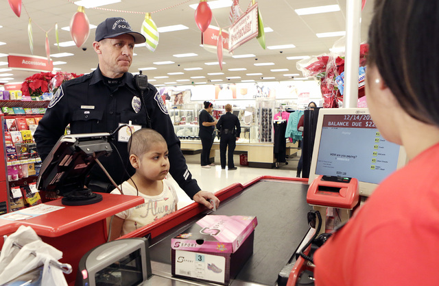 North Las Vegas police officer Jay Simpson checks out with Roxy Huerta, 6, after shopping at Target during the annual ғhop with a CopӠevent on 7090 N. Fifth St. Wednesday, Dec. 14, 201 ...