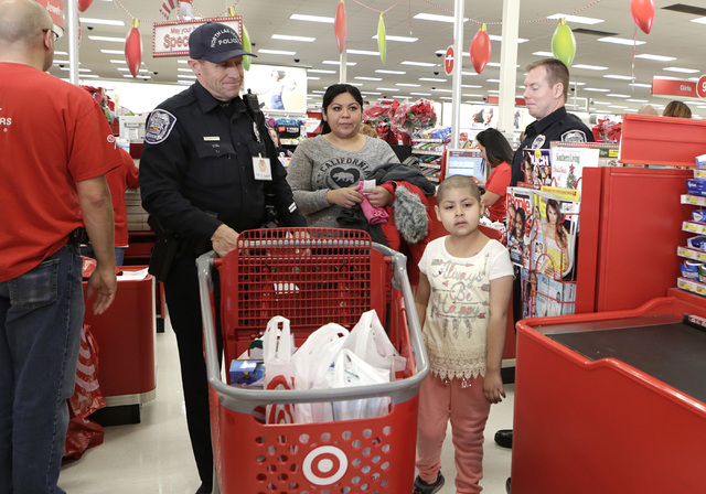 North Las Vegas police officers Jay Simpson, left, and Tim Frabbiele, right, check out with Roxy Huerta, 6, and her mother Joanna after shopping at Target during the annual ғhop with a Cop&# ...