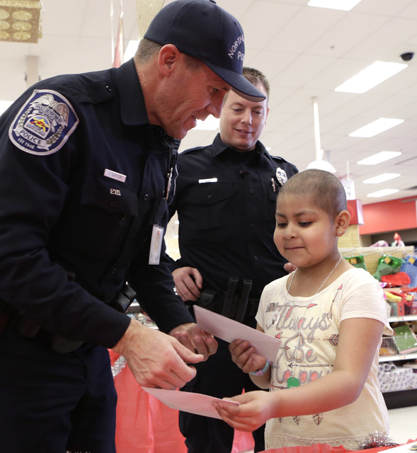 North Las Vegas police officer Jay Simpson exchanges Christmas card with Roxy Huerta, 6, as Tim Frabbiele, center, looks on after shopping at Target during the annual ғhop with a CopӠe ...