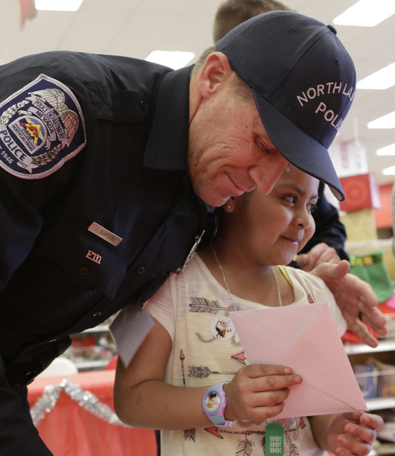 North Las Vegas police officer Jay Simpson hugs Roxy Huerta, 6,  after shopping and exchanging Christmas card at Target during the annual ғhop with a CopӠevent on 7090 N. Fifth St. Wed ...