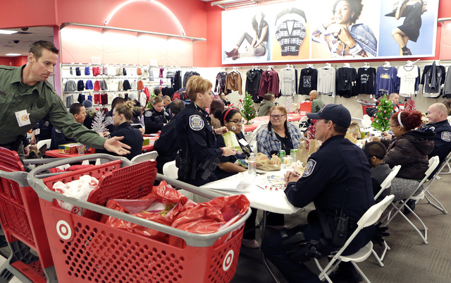 North Las Vegas police officers, detention officers and marshals chat with local kids and their families after shopping at Target during the annual ғhop with a CopӠevent on 7090 N. Fif ...