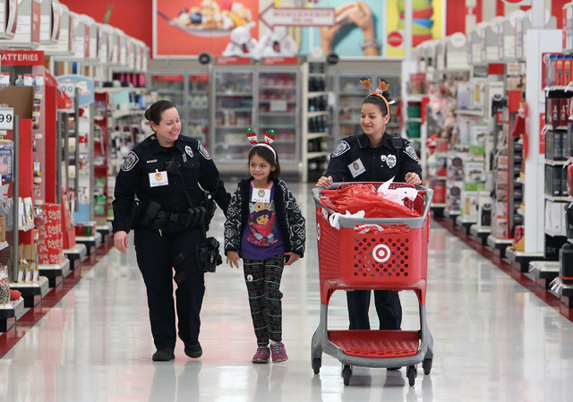 North Las Vegas police officers Kim Ewertz, left, and Michelle Rodriguez, shop with April Khoy, 7, at Target during the annual ғhop with a CopӠevent on 7090 N. Fifth St. Wednesday, Dec ...