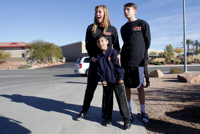 Nicolette Harridge watches with her sons Chance Harridge, 12, and Edward Angulo, 6, as a firetruck with Santa Claus and gifts approaches Fire Station 98 on Tuesday, Dec. 20, 2016, in Henderson. (R ...