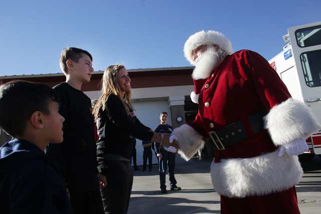Santa Claus shakes hands with Nicolette Harridge next to her sons Chance Harridge,12, and Edward Angulo, 6, at Fire Station 98 on Tuesday, Dec. 20, 2016, in Henderson. (Rachel Aston/Las Vegas Revi ...