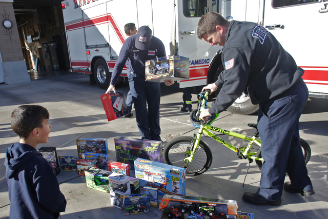 Edward Angulo, 6, watches as firefighters place gifts out for him and his family at Fire Station 98 on Tuesday, Dec. 20, 2016, in Henderson. (Rachel Aston/Las Vegas Review-Journal) @rookie__rae
