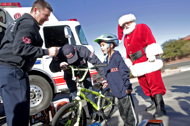 Fighfighter Donovan Kutsenda, left, and Engineer Rodger Delk show Edward Angulo, 6, his new bike as Santa Claus watches at Fire Station 98 on Tuesday, Dec. 20, 2016, in Henderson. (Rachel Aston/La ...