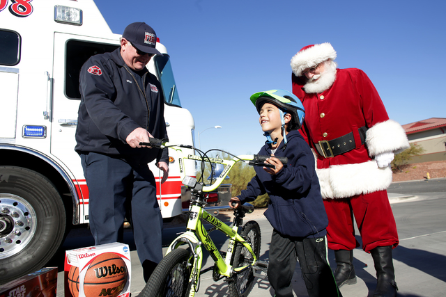 Engineer Rodger Delk shows Edward Angulo, 6, his new bike as Santa Claus watches at Fire Station 98 on Tuesday, Dec. 20, 2016, in Henderson. (Rachel Aston/Las Vegas Review-Journal) @rookie__rae