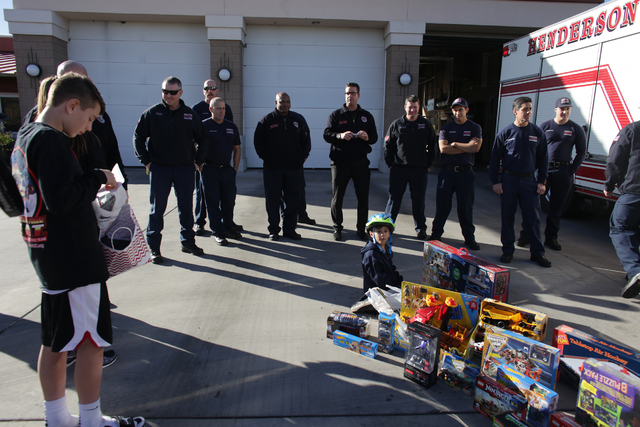 Firefighters that responded to the fire that destroyed the home of Nicolette Harridge and her sons present them gifts for Christmas at Fire Station 98 on Tuesday, Dec. 20, 2016, in Henderson. (Rac ...