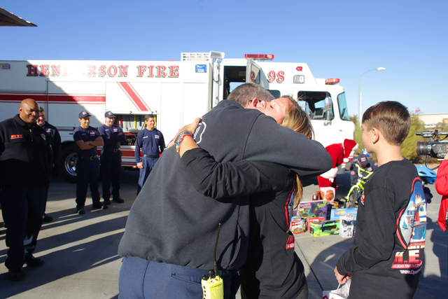 Captain Kevin Szczudlak hugs Nicolette Harridge at Fire Station 98 after his platoon delivered gifts to her family on Tuesday, Dec. 20, 2016, in Henderson. Szczudlak responded to the fire that des ...