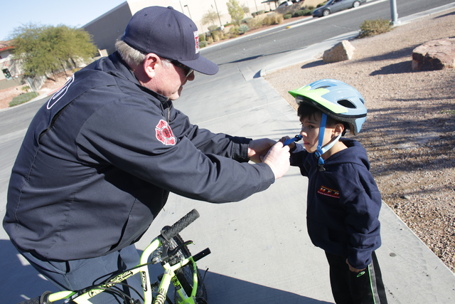 Engineer Rodger Delk puts a helmet on Edward Angulo, 6, at Firestation 98 on Tuesday, Dec. 20, 2016, in Henderson. (Rachel Aston/Las Vegas Review-Journal) @rookie__rae
