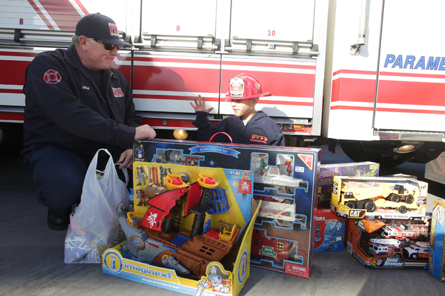 Engineer Rodger Delk shows Edward Angulo, 6, his new gifts at Firestation 98 on Tuesday, Dec. 20, 2016, in Henderson. (Rachel Aston/Las Vegas Review-Journal) @rookie__rae