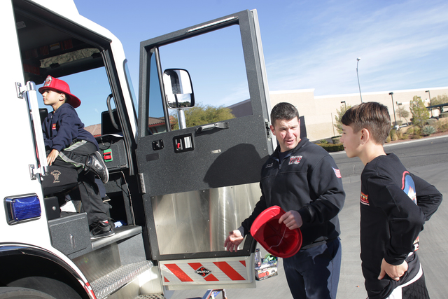 Firefighter Donovan Kutsenda gives Edward Angulo, 6, and Chance Harridge, 12, a tour of the firetruck at Fire Station 98 on Tuesday, Dec. 20, 2016, in Henderson. (Rachel Aston/Las Vegas Review-Jou ...