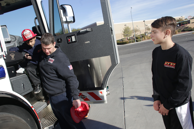 Firefighter Donovan Kutsenda picks up Edward Angulo, 6, after showing him and his brother Chance Harridge, 12, a tour of the firetruck at Fire Station 98 on Tuesday, Dec. 20, 2016, in Henderson. ( ...