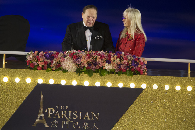 Las Vegas Sands Corp. CEO Sheldon Adelson, left, with his wife, Dr. Miriam Adelson, speaks during the grand opening ceremony for Sands China Ltd. new resort, Parisian, on Tuesday, Sept. 13, 2016,  ...