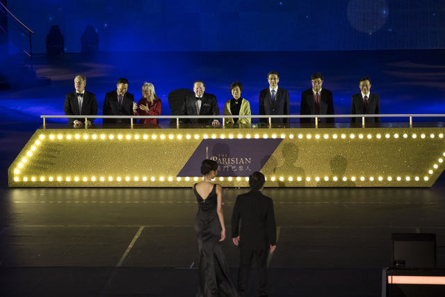 Las Vegas Sands Corp. CEO Sheldon Adelson, fourth from left, with his wife, Dr. Miriam Adelson, third from left, and other dignitaries participate during the grand opening ceremony for Sands China ...