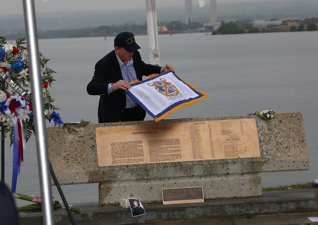 On a rainy Thursday morning, December 8, 2016, John Galloway places a flag with the names of the men who perished on December 7, 1941 onto the marker at Hospital Point where the USS Nevada was bea ...
