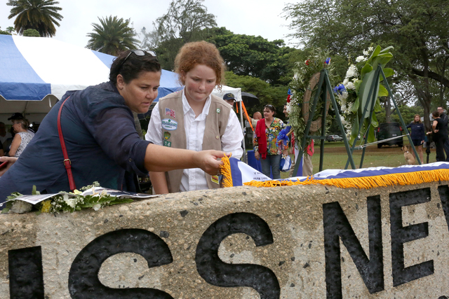 Clair Montgomery, right, from Girl Scout Troop 214, and her mother Lucinda Montgomery read inscriptions on the marker on Thursday morning, December 8, 2016, at Hospital Point, where the USS Nevada ...