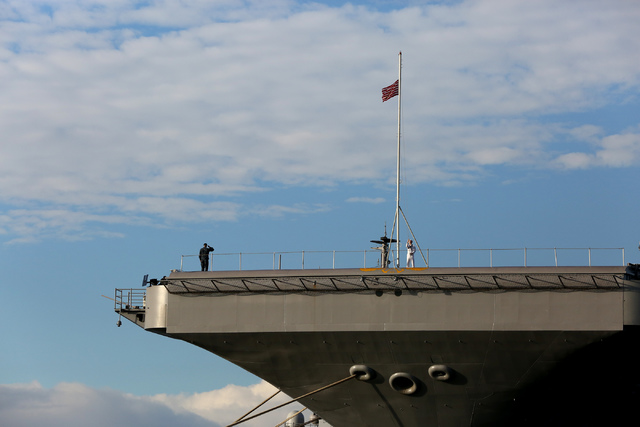 As the national anthem plays, a sailor raises the colors on the bow of the USS John C. Stennis aircraft carrier in Pearl Harbor, Hawaii, on Monday morning. Veterans, family members and dignitaries ...