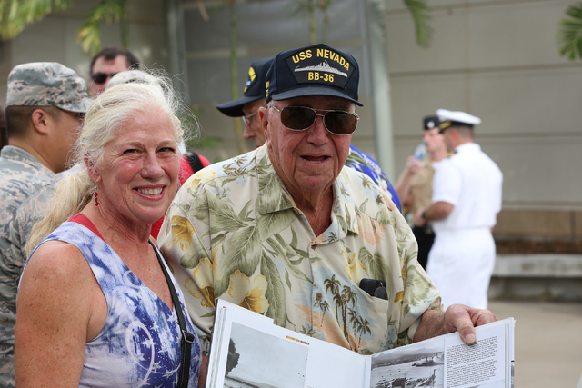 USS Nevada veteran Charles (Cliff) Burks, right, with his daughter, Kerry Albritton, displays a book with the USS Nevada during the December 7, 1941 surprise attack on Pearl Harbor at the Pearl Ha ...