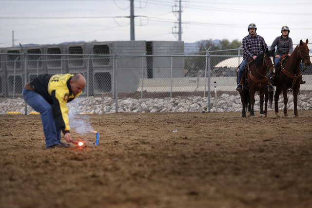 A Las Vegas Policed Department officer lights a firecracker to test the horses reaction as Tim Ruiz, 36, left, and Maile Hanks, 29, sits mounted during training at the Mounted Unit training facili ...