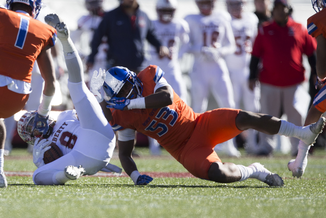 Liberty's Bryson Dela Cruz (8) is tackled by Bishop Gorman's Farrell Hester (53) after a run in the Class 4A state football championship game at Sam Boyd Stadium on Saturday, Dec. 3, 2016, in Las  ...