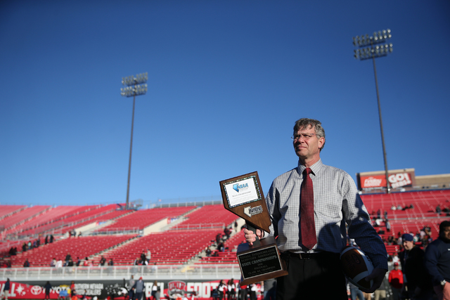 Bart Thompson, executive director for the Nevada Interscholastic Activities Association, gets ready to present the champion trophy to Bishop Gorman after their 84-8 win against Liberty in the Clas ...
