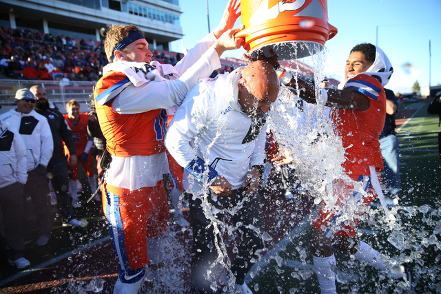 Bishop Gorman's head football coach Kenny Sanchez, center, gets a Gatorade (water) shower by his players Tate Martell (18), left, and Alex Perry (4) as the game comes to an end for a win 88-8 agai ...