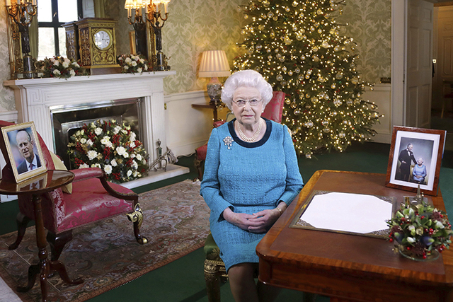In this photo released early Sunday Dec. 25, 2016, Britain's Queen Elizabeth II poses for a photo, sitting at a desk in the Regency Room of Buckingham Palace in London, after recording her traditi ...