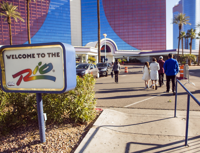 Members of a family walk on Thursday, Dec. 29, 2016, to the Rio to see whether they could pick up their bags. The resort was evacuated after another electrical fire broke out Thursday morning. (Je ...