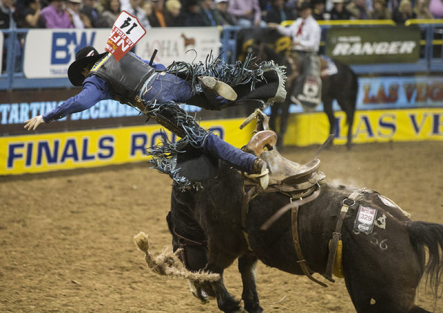 Rusty Wright is thrown from Stampede Warrior during the saddle bronc riding competition on the ninth day of the National Finals Rodeo at the Thomas & Mack Center on Friday, Dec. 9, 2016, in La ...