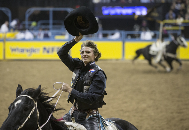 Ryder Wright salutes the crowd after winning the saddle bronc riding competition on the ninth day of the National Finals Rodeo at the Thomas & Mack Center on Friday, Dec. 9, 2016, in Las Vegas ...