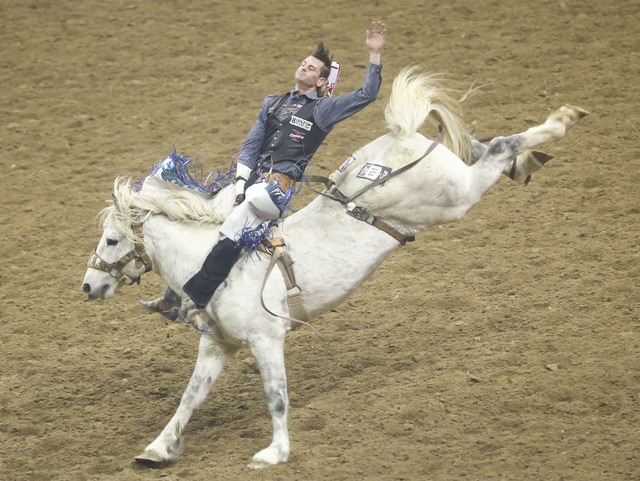 R.C. Landingham rides Must Have while competing in the bareback riding event during the 3rd go-round of the National Finals Rodeo at the Thomas & Mack Center in Las Vegas on Saturday, Dec. 3,  ...