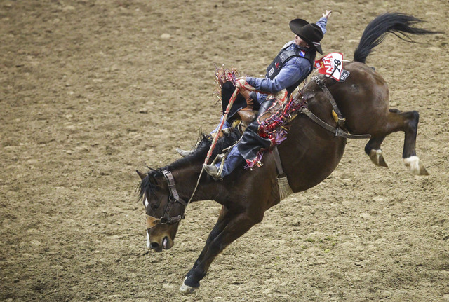 Cody Wright rides Griz while competing in the saddle bronc riding event during the 3rd go-round of the National Finals Rodeo at the Thomas & Mack Center in Las Vegas on Saturday, Dec. 3, 2016. ...