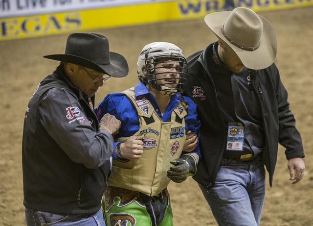 Jordan Spears is helped from the arena after getting stomped by Cowbanger during the bull riding competition at the National Finals Rodeo at the Thomas & Mack Center on Thursday, Dec. 8, 2016, ...