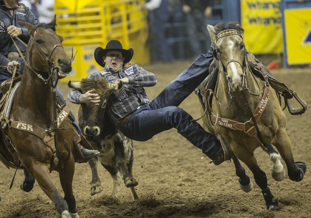 Nick Guy jumps from his horse onto a steer during steer wrestling at the National Finals Rodeo at the Thomas & Mack Center on Thursday, Dec. 8, 2016, in Las Vegas. (Benjamin Hager/Las Vegas Re ...