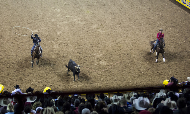 Cody Snow, left, and Dugan Kelly compete during the team roping competition on the final night of the National Finals Rodeo at the Thomas & Mack Center in Las Vegas on Saturday, Dec. 9, 2016.  ...