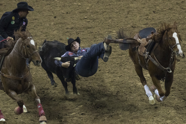 J.D. Struxness competes during the steer wrestling competition on the final night of the National Finals Rodeo at the Thomas & Mack Center in Las Vegas on Saturday, Dec. 9, 2016. (Miranda Alam ...