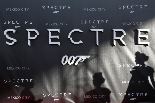 """Dancers cast their shadows on a banner promoting the new James Bond 007 film """"Spectre"""" during a red carpet at the Mexican premiere in Mexico City, November 2, 2015. (Ginnette Riquelme/Reuters)"""