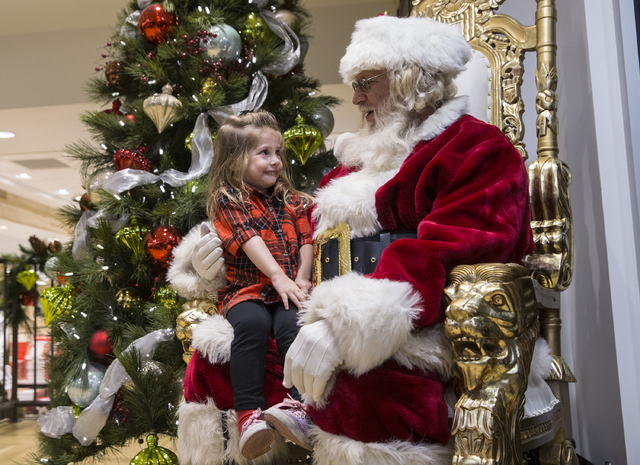 "Santa Claus Barry Solomon, right, listens to Joanna Fountain's Christmas list at the Ethel M Chocolate Factory on Friday, Dec. 16, 2016, in Henderson. ""I just love it,"" said Solomon. ""It's the mos ..."