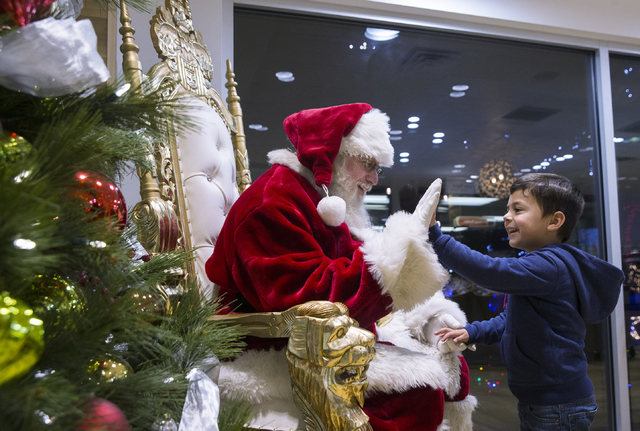 "Santa Claus Barry Solomon, left, gives Max Arguelles, 3, a high five at the Ethel M Chocolate Factory on Friday, Dec. 16, 2016, in Henderson. ""I will do this for as long as I can,"" said Solomon. "" ..."