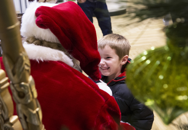 "Axel Arney, 3, gives Santa Claus Barry Solomon a big smile at the Ethel M Chocolate Factory on Friday, Dec. 16, 2016, in Henderson. ""I want to give the spirit of giving and joy in every way I can, ..."