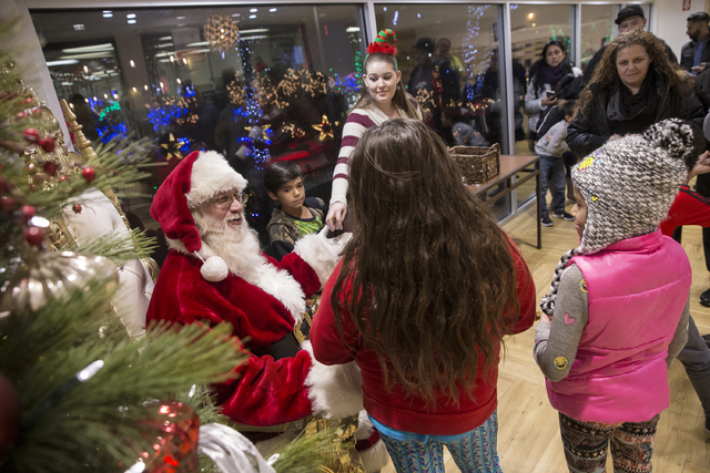"Santa Claus Barry Solomon, left, hands out candy to children at the Ethel M Chocolate Factory on Friday, Dec. 16, 2016, in Henderson. ""I want to give the spirit of giving and joy in every way I ca ..."