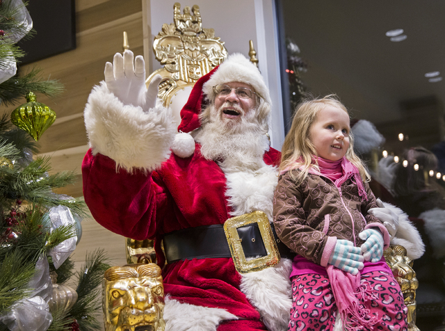"Santa Claus Barry Solomon, left, waives to parents while sitting with Layla Card, 3, at the Ethel M Chocolate Factory on Friday, Dec. 16, 2016, in Henderson. ""I will do this for as long as I can,"" ..."