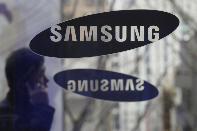 A man passes by the Samsung Electronics Co. logos at its headquarters Dec. 12, 2013, in Seoul, South Korea. A unanimous Supreme Court on Tuesday, Dec. 6, 2016, sided with smartphone maker Samsung  ...